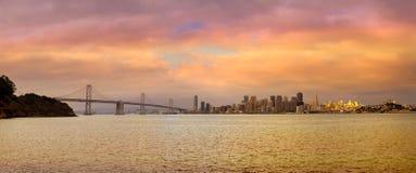 旧金山加州由海湾桥梁的市地平线在日落 免版税库存照片