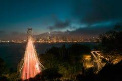 旧金山地平线在与交通的夜之前横跨海湾桥梁 免版税库存图片