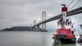 旧金山,加利福尼亚- 2014年8月3日:由海湾桥梁,旧金山,加利福尼亚的消防队员小船 免版税库存图片