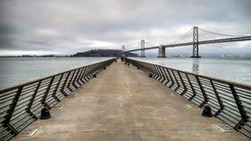 旧金山,加州- 2014年9月02日:码头14在有海湾桥梁的旧金山在背景中 库存图片