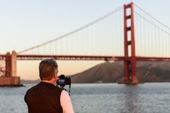 旧金山,美国- 2018年10月12日:一个人为金门大桥照相在日出旧金山 免版税图库摄影
