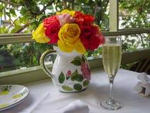 早午餐桌设置了与香槟玫瑰和长笛花束  免版税库存图片
