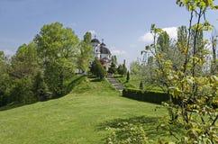 早春天绿色、钟楼和教会有现代建筑学的在区Drujba 免版税库存照片