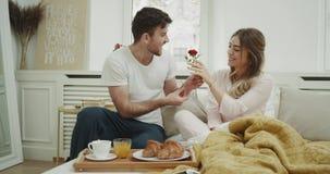 早晨一对逗人喜爱的夫妇喝早餐在床,人给玫瑰的他的妻子,愉快的饮料汁液和咖啡 影视素材