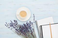 早晨咖啡、干净的笔记本和淡紫色在蓝色背景顶视图开花 妇女运转的书桌 舒适早餐舱内甲板位置样式 免版税库存图片