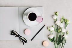 早晨咖啡、空的笔记本、铅笔、玻璃、白花和蛋糕macaron在轻的台式视图 免版税库存图片