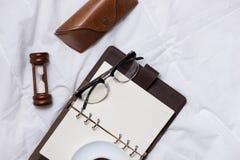 早晨咖啡和日志与时钟和木铅笔在布料t 免版税库存图片