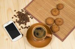 早晨咖啡和饼干在木书桌上有手机的 免版税库存图片