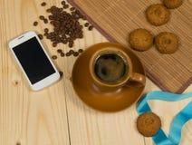 早晨咖啡和饼干在木书桌上有手机的 免版税库存照片