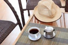早晨咖啡在越南在藤条桌上的咖啡过滤器服务与两把藤条椅子 免版税库存图片