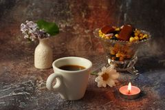 早晨咖啡急忙:一杯咖啡、花在花瓶,干果子和甜点在花瓶,一个灼烧的蜡烛 图库摄影