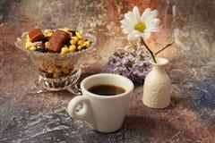 早晨咖啡急忙:一杯咖啡、花在花瓶,干果子和甜点在花瓶,一个灼烧的蜡烛 免版税图库摄影