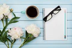 早晨咖啡杯、空的笔记本、铅笔、玻璃和白色牡丹在蓝色木桌,舒适夏天早餐上开花 免版税库存图片
