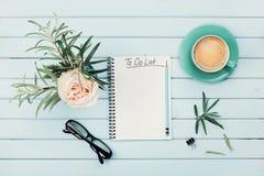 早晨咖啡杯、笔记本与从上面要做名单的,铅笔、镜片和葡萄酒玫瑰色花在花瓶在蓝色土气桌上 库存照片