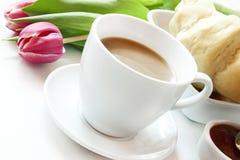 早晨咖啡杯新月形面包和花 免版税库存照片