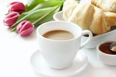 早晨咖啡杯新月形面包和花 库存照片