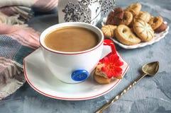 早晨咖啡用在原始的白色杯的牛奶有一个蓝色按钮的 库存图片