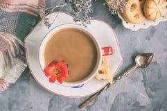 早晨咖啡用在原始的白色杯的牛奶有在曲奇饼的背景的一个蓝色按钮的 免版税库存图片