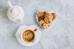 早晨咖啡用在原始的白色杯的牛奶有在曲奇饼的背景的一个蓝色按钮的 库存图片