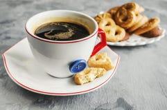 早晨咖啡用在原始的白色杯的牛奶有在曲奇饼的背景的一个蓝色按钮的 免版税库存照片