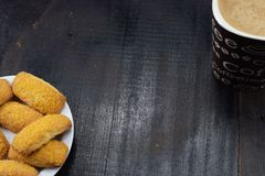 早晨咖啡用牛奶和曲奇饼在一张黑暗的桌上 库存图片
