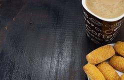 早晨咖啡用牛奶和曲奇饼在一张黑暗的桌上 图库摄影