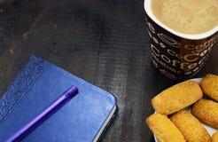 早晨咖啡用牛奶和曲奇饼在一张黑暗的桌上 免版税库存照片