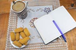 早晨咖啡用牛奶和饼干在一张木桌上,笔记本,日志 免版税库存照片