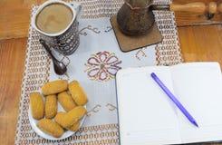早晨咖啡用牛奶和饼干在一张木桌上,笔记本,日志 免版税图库摄影