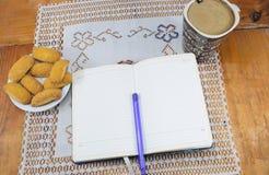 早晨咖啡用牛奶和饼干在一张木桌上,笔记本,日志 免版税库存图片