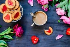 早晨咖啡的概念在一个浪漫样式的在黑木背景 牡丹花和瓣,曲奇饼,心脏candl 免版税库存照片