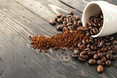 早晨咖啡豆和杯子在木头冠上 免版税库存照片