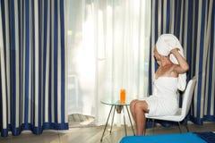 早晨唤醒一年轻女人在酒店房间 免版税库存照片