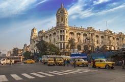 早晨在大城市遗产建筑大厦前面的城市交通在广场加尔各答,印度 免版税库存图片