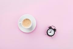 早晨在桃红色运作的桌面看法的咖啡和闹钟在舱内甲板放置样式 库存照片