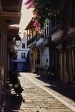 早晨太阳的第一光芒照亮的街道的看法在一个传统希腊镇 图库摄影