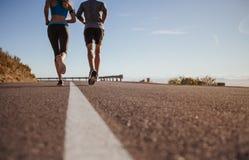 早晨奔跑的两青年人 免版税库存图片