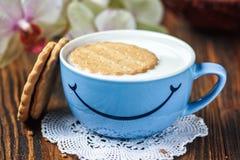 早晨好或玩得高兴消息概念-明亮的蓝色杯子牛奶用曲奇饼 杯与微笑的牛奶 健康和饮食co 免版税库存图片