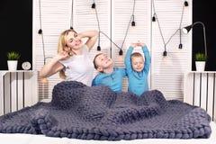 早晨好!母亲和两个小儿子在床上舒展 正面唤醒 免版税库存图片