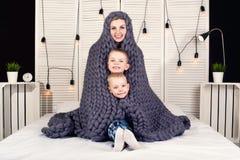 早晨好!母亲和两个小儿子掩藏在一条被编织的毯子下 正面唤醒 免版税库存图片