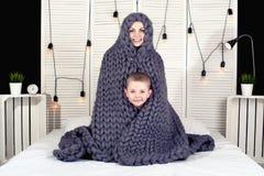 早晨好!母亲和小儿子皮在一条被编织的毯子下 正面唤醒 免版税库存照片