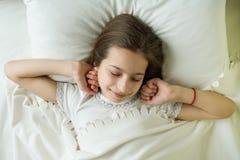 早晨好,十几岁的女孩在她的床,顶视图上醒并且微笑说谎在一个枕头 免版税库存照片