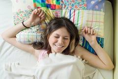 早晨好,十几岁的女孩对说谎在一个枕头的照相机在她的床,顶视图上醒并且微笑 库存图片