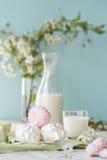 早晨好!俄国蛋白软糖或和风与瓶和杯牛奶在树背景 春天构成 免版税库存图片