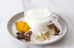 早晨心情和金黄牛奶为在厨房的早餐做准备 复制您的文本的空间 镀和许多spieces,杯子牛奶 免版税库存照片