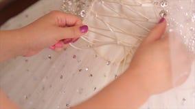 早晨新娘 帮助有她的礼服的伴娘新娘 新娘` s系带礼服 栓弓的女傧相  免版税库存图片
