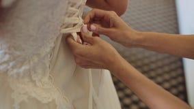早晨新娘 栓在婚礼礼服的女傧相弓 妇女` s手系带在新娘` s束腰的丝绸丝带 帮助 影视素材