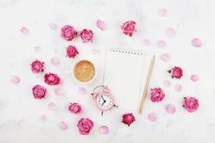 早晨早餐、空的笔记本、瓣、闹钟和桃红色玫瑰的咖啡杯在白色台式视图舱内甲板位置开花 免版税库存照片