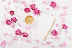 早晨早餐、空的笔记本、瓣和桃红色玫瑰的咖啡杯在舱内甲板位置样式的白色台式视图开花 库存照片