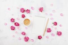 早晨早餐、空的笔记本、铅笔和桃红色玫瑰的咖啡杯在舱内甲板位置样式的白色石台式视图开花 免版税库存图片